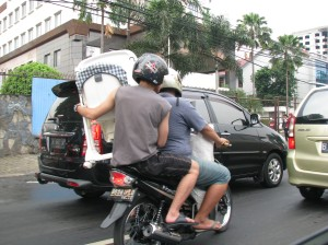 Carrying a baby carrier on a motorcycle, the vehicle of choice for millions in Jakarta