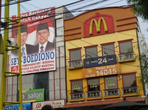 A campaign banner for the current President of Indonesia on a building next to McDonalds