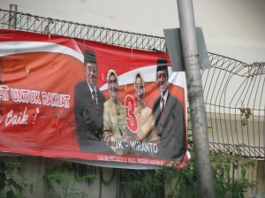 Not a bare head to be seen!  Presidential campaign banner for candidates J. Kalla, current vice-president, and Wiranto, Kalla's vice-presidental choice, with their respective wives shows all wearing head-gear, the women head scarves and the men mosque-hats.