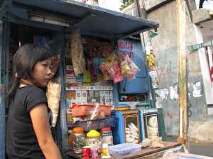 A girl in front of a street corner stall in Jakarta selling cigarettes, candy, and crackers.  There are tens of thousands, if not more, of such street stalls in Jakarta.